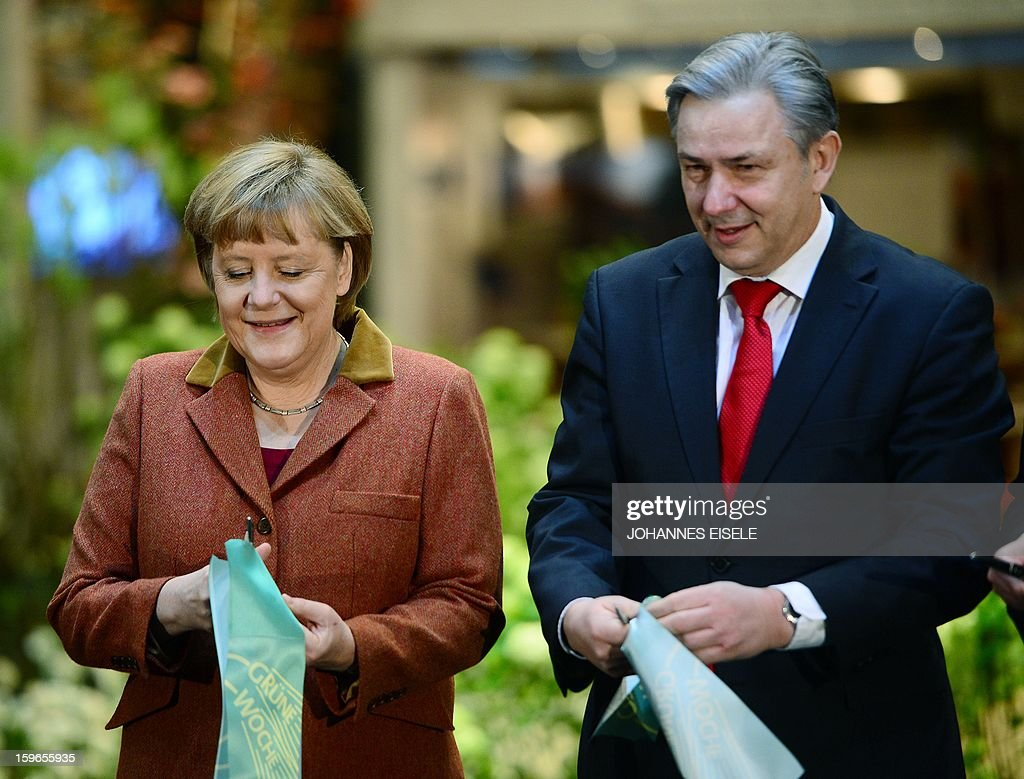 German Chancellor Angela Merkel and Berlin Mayor Klaus Wowereit (R) cut a ribbon on January 18, 2013 during the opening of the Green Week Agricultural Fair in Berlin. AFP PHOTO / JOHANNES EISELE