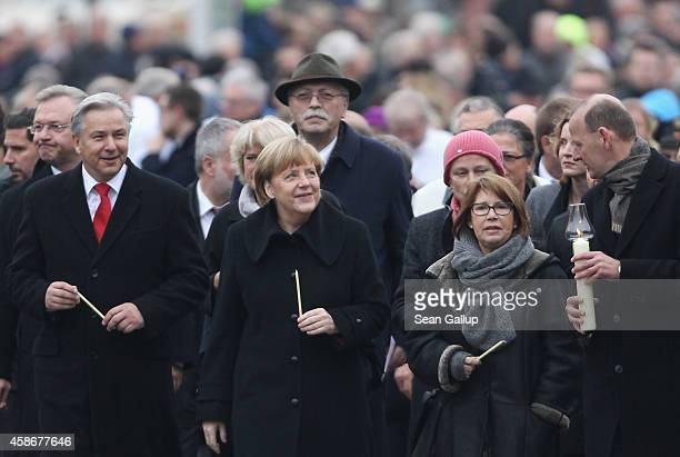 German Chancellor Angela Merkel and Berlin Mayor Klaus Wowereit arrive to place candles at the Berlin Wall Memorial at Bernauer Strasse on the 25th...
