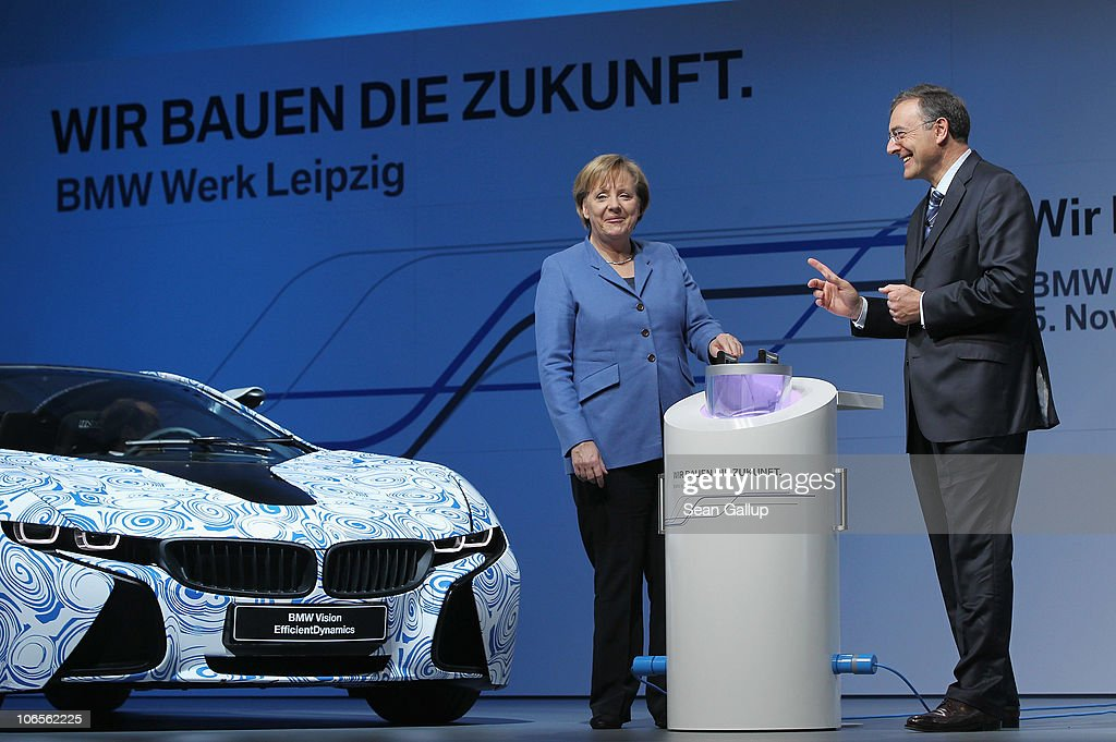 German Chancellor Angela Merkel and BMW Chairman Norbert Reithofer lower a container with messages into a capsule while speaking at the BMW auto...