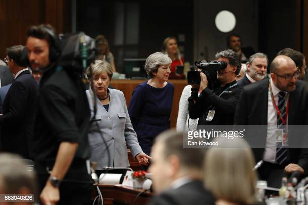 German Chancellor Angela Merkel and Britain's Prime Minister Theresa May arrive for a round table meeting on October 19 2017 in Brussels Belgium...