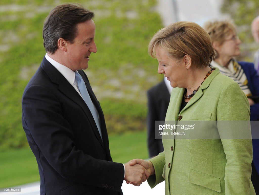 German Chancellor Angela Merkel and British Prime Minister David Cameron shake hands before they inspect an honour guard at the Chancellery in Berlin on May 21, 2010. Cameron is on his first visit to Germany since becoming prime minister.