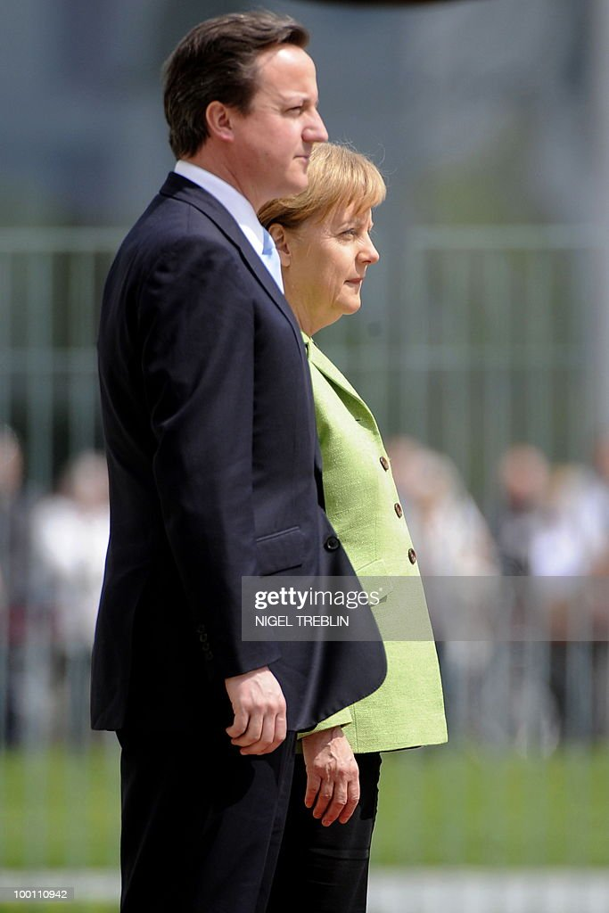 German Chancellor Angela Merkel and British Prime Minister David Cameron listen to their national anthems after inspecting an honour guard at the Chancellery in Berlin on May 21, 2010. Cameron is on his first visit to Germany since becoming prime minister.