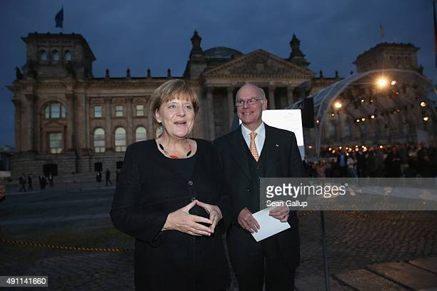 German Chancellor Angela Merkel and Bundestag President Norbert Lammer arrive for performances outside the Reichstag during celebrations on the 25th...