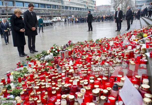 German Chancellor Angela Merkel and Canadian Prime Minister Justin Trudeau pause after laying flowers at a memorial to the victims of the December...