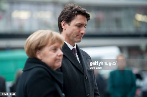 German Chancellor Angela Merkel and Canadian Prime Minister Justin Trudeau react after laying flowers at a memorial to the victims of the December...