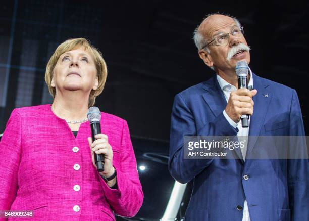 German Chancellor Angela Merkel and CEO of German car maker Daimler AG and head of MercedesBenz cars Dieter Zetsche stand in front of an electric...