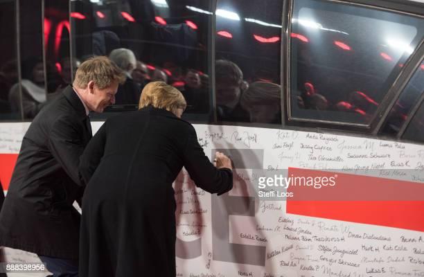 German Chancellor Angela Merkel and Chairman of German railway operator Deutsche Bahn Richard Lutz sign an ICE high speed train at the main railway...