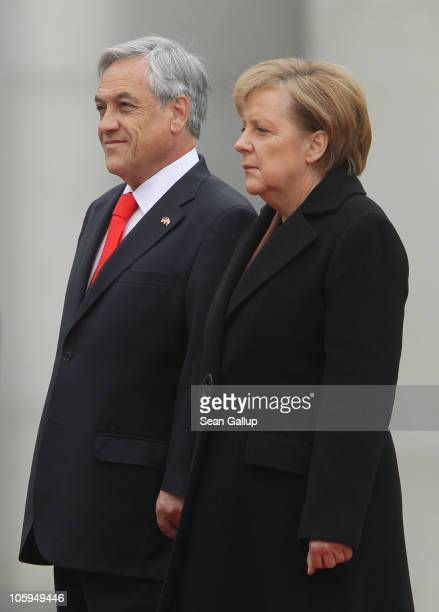 German Chancellor Angela Merkel and Chilean President Sebastian Pinera review a guard of honour upon his arrival at the Chancellery on October 22...