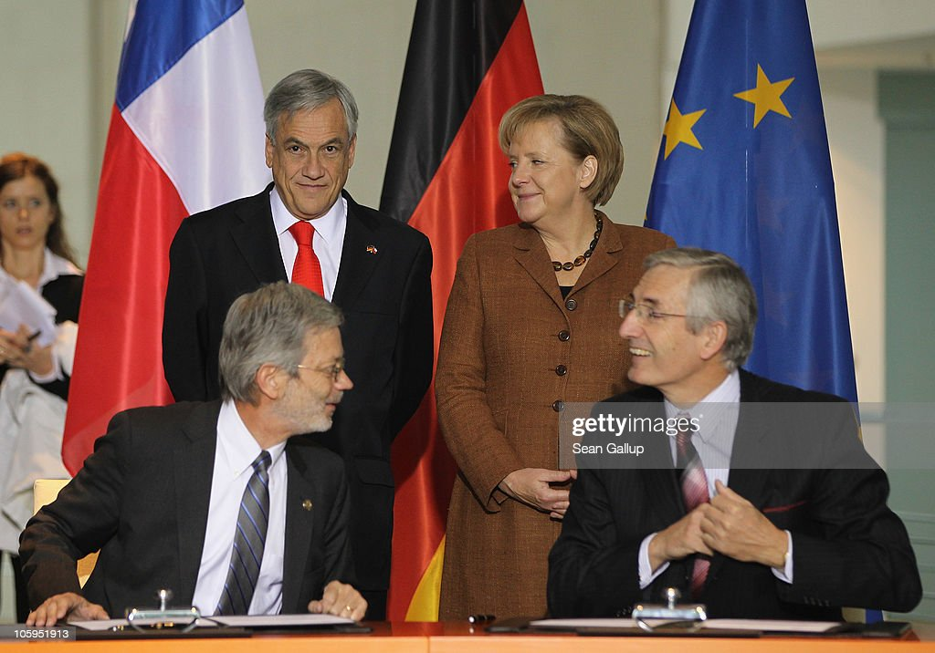 German Chancellor <a gi-track='captionPersonalityLinkClicked' href=/galleries/search?phrase=Angela+Merkel&family=editorial&specificpeople=202161 ng-click='$event.stopPropagation()'>Angela Merkel</a> and Chilean President Sebastian Pinera look on as Chilean Economy Minister Juan Andres Fontaine (L) and Fraunhofer Institute Alfred Gossner sign an agreement of intent to establish a Fraunhofer Institute in Chile at the Chancellery (Bundeskanzleramt) on October 22, 2010 in Berlin, Germany. Pinera is visiting Europe following the rescue of 33 trapped miners in Chile last week.