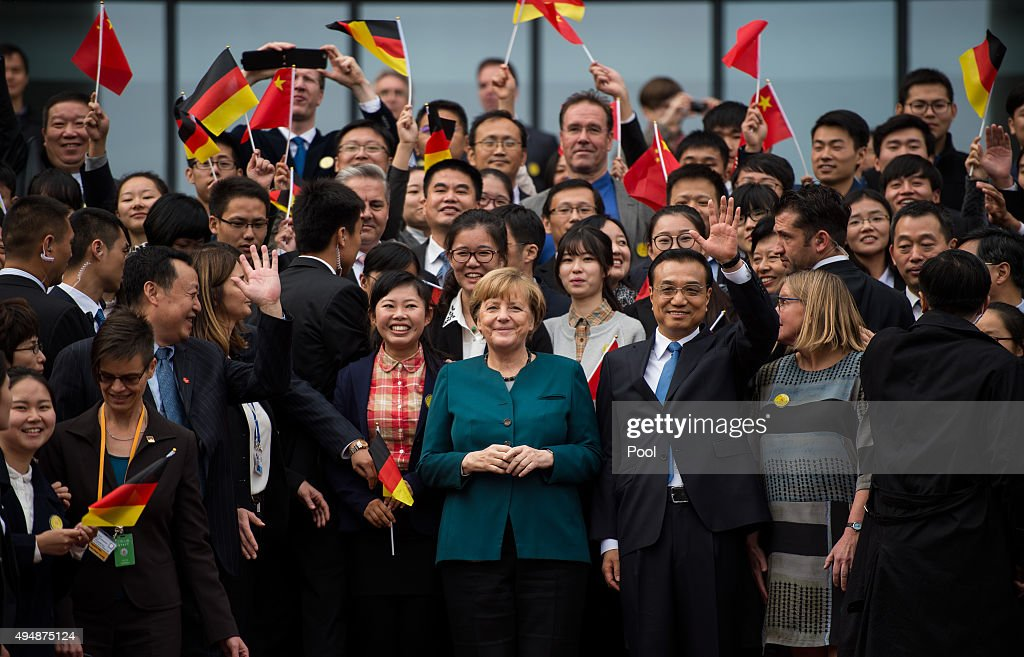 German Chancellor Angela Merkel (C) and Chinese Premier Li Keqiang (R) pose with students after their visit of the German University on October 30, 2015 in Hefei, China. Merkel is in Hefei, capital of east China's Anhui Province, for a one day visit, accompanied by her Chinese counterpart Li Keqiang.