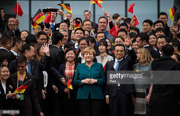 German Chancellor Angela Merkel and Chinese Premier Li Keqiang pose with students after their visit of the German University on October 30 2015 in...