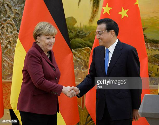 German Chancellor Angela Merkel and Chinese Premier Li Keqiang shake hands affter a news conference at the Great Hall of the People on October 29...