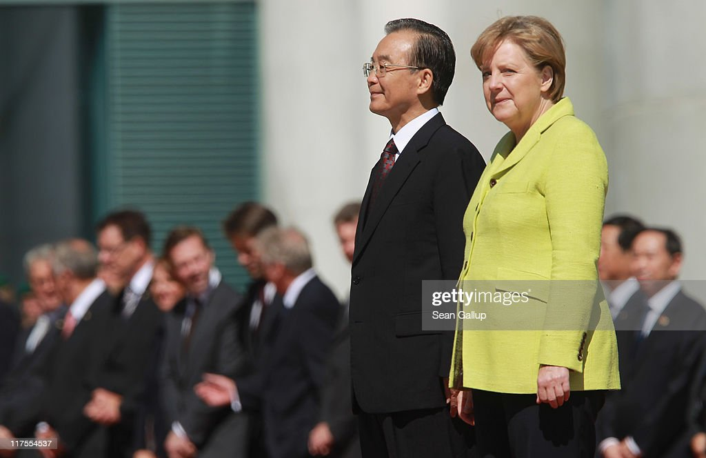 German Chancellor Angela Merkel and Chinese Premier Wen Jiabao listen to their countries' respective naitonal anthems upon Wen's arrival at the Chancellery on June 28, 2011 in Berlin, Germany. The Chinese leader is visiting a variety of European countries and in Germany is participating in the first-ever German-Chinese government consultaitons.