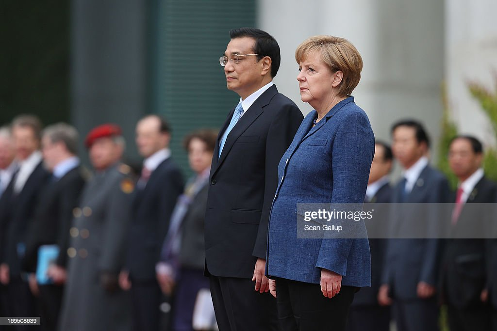 German Chancellor <a gi-track='captionPersonalityLinkClicked' href=/galleries/search?phrase=Angela+Merkel&family=editorial&specificpeople=202161 ng-click='$event.stopPropagation()'>Angela Merkel</a> and Chinese Prime Minister <a gi-track='captionPersonalityLinkClicked' href=/galleries/search?phrase=Li+Keqiang&family=editorial&specificpeople=2481781 ng-click='$event.stopPropagation()'>Li Keqiang</a> listen to their nations' respective national anthems upon his arrival at the Chancellery on May 26, 2013 in Berlin, Germany. On his first official visit to Germany as prime minister, Mr. Li is scheduled to meet with German federal and regional government officials and business representatives.