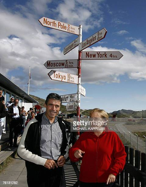 German Chancellor Angela Merkel and Denmark's Prime Minister Anders Fogh Rasmussen stand next to a guidepost at the airport of Kangerlussuaq...
