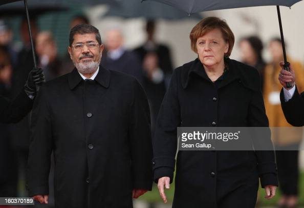 German Chancellor Angela Merkel and Egyptian President Mohamed Mursi review a guard of honour under pouring rain upon Mursi's arrival at the...