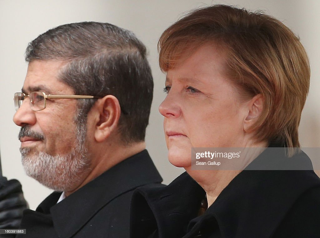 German Chancellor <a gi-track='captionPersonalityLinkClicked' href=/galleries/search?phrase=Angela+Merkel&family=editorial&specificpeople=202161 ng-click='$event.stopPropagation()'>Angela Merkel</a> and Egyptian President Mohamed Mursi listen to their countries' respective national anthems under pouring rain upon his arrival at the Chancellery on January 30, 2013 in Berlin, Germany. Mursi has come to Berlin despite the ongoing violent protests in recent days in cities across Egypt that have left at least 50 people dead. Mursi is in Berlin to seek both political and financial support from Germany.