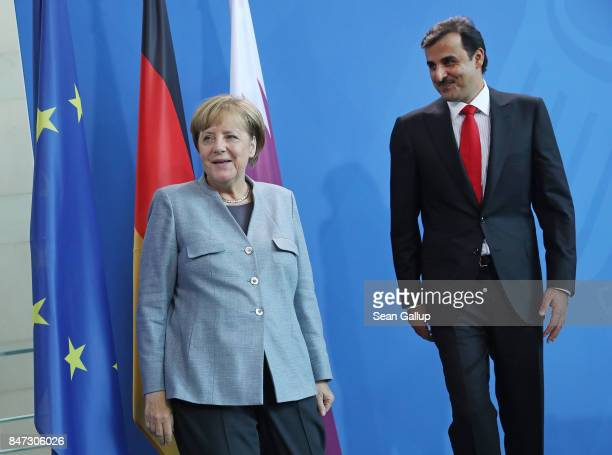 German Chancellor Angela Merkel and Emir of Qatar Sheikh Tamim bin Hamad Al Thani depart after speaking to the media following talks at the...