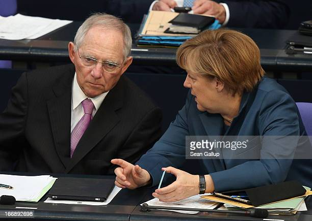 German Chancellor Angela Merkel and Finance Minister Wolfgang Schaeuble chat during debates over EU finanical aid to Cyprus at the Bundestag on April...