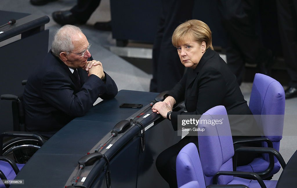 German Chancellor <a gi-track='captionPersonalityLinkClicked' href=/galleries/search?phrase=Angela+Merkel&family=editorial&specificpeople=202161 ng-click='$event.stopPropagation()'>Angela Merkel</a> (R) and Finance Minister Wolfgang Schaeuble chat during a vote at the Bundestag over her third term as chancellor during ceremonies in which the new German government will be sworn in on December 17, 2013 in Berlin, Germany. The new government is a coalition between the German Christian Democrats (CDU), the Bavarian Christian Democrats (CSU) and German Social Democrats (SPD) following federal elections held in September.