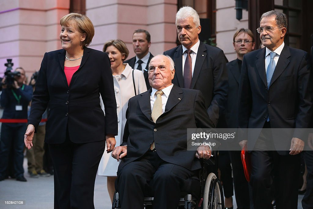German Chancellor <a gi-track='captionPersonalityLinkClicked' href=/galleries/search?phrase=Angela+Merkel&family=editorial&specificpeople=202161 ng-click='$event.stopPropagation()'>Angela Merkel</a> (L) and former Italian Prime Minister <a gi-track='captionPersonalityLinkClicked' href=/galleries/search?phrase=Romano+Prodi&family=editorial&specificpeople=203301 ng-click='$event.stopPropagation()'>Romano Prodi</a> (R) accompany former German Chancellor <a gi-track='captionPersonalityLinkClicked' href=/galleries/search?phrase=Helmut+Kohl&family=editorial&specificpeople=202518 ng-click='$event.stopPropagation()'>Helmut Kohl</a> at his arrival at a gala evening in his honour at the Deutsches Museum on September 27, 2012 in Berlin, Germany. Guests from politics, church and society attended the event to honour Kohl on the 30th anniversary of Kohl becoming chancellor. During his chancellorship Kohl facillitated the end of the Cold War, the fall of the Berlin Wall and German reunification.