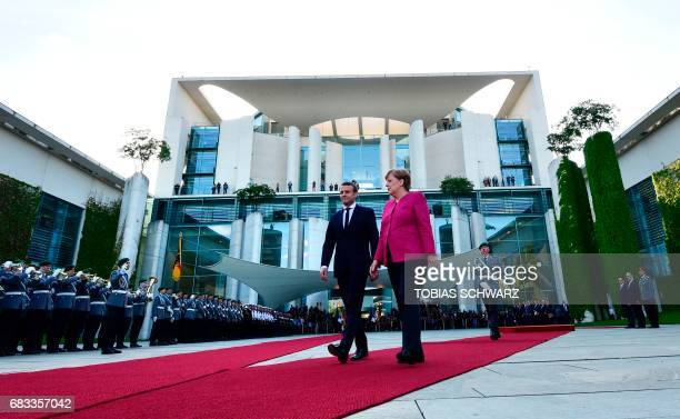German Chancellor Angela Merkel and French President Emmanuel Macron walk together during the welcoming ceremony prior talks on May 15 2017 at the...