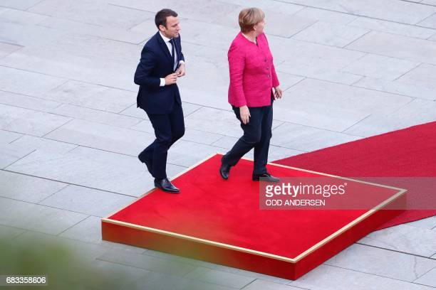 German Chancellor Angela Merkel and French President Emmanuel Macron step on to the podium to listen to the national anthems after he arrived for...