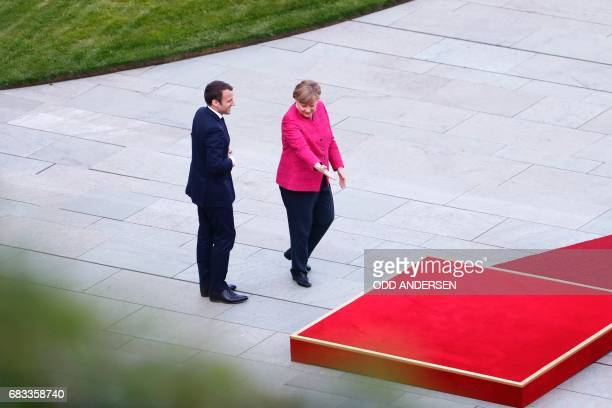 German Chancellor Angela Merkel and French President Emmanuel Macron step up to the podium to listen to the national anthems after he arrived for...
