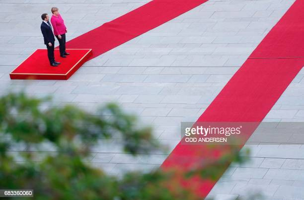 German Chancellor Angela Merkel and French President Emmanuel Macron listen to the national anthems after he arrived for talks a day after the new...