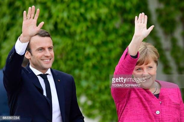 TOPSHOT German Chancellor Angela Merkel and French President Emmanuel Macron wave to the crowds during a welcoming ceremony a day after the new...