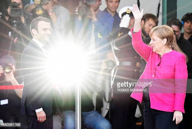 TOPSHOT German Chancellor Angela Merkel and French President Emmanuel Macron are about to enter the chancellery after the welcoming ceremony on May...