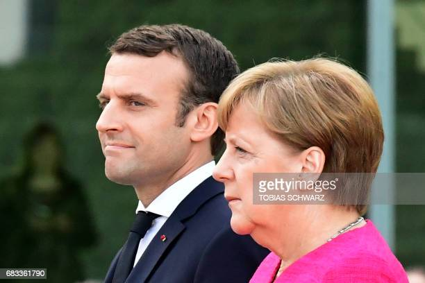 German Chancellor Angela Merkel and French President Emmanuel Macron listen to the national anthems during a welcoming ceremony a day after the new...