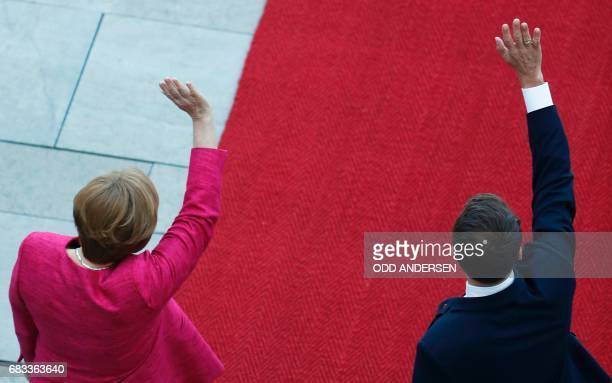 German Chancellor Angela Merkel and French President Emmanuel Macron wave to the crowds during a welcoming ceremony after he arrived for talks on...