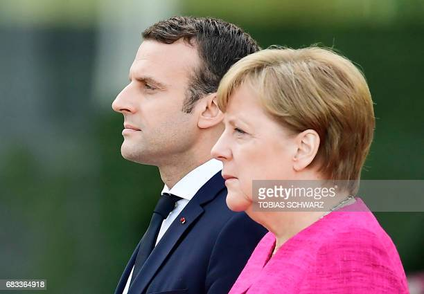 German Chancellor Angela Merkel and French President Emmanuel Macron listen to the national anthems prior talks on May 15 2017 at the chancellery in...