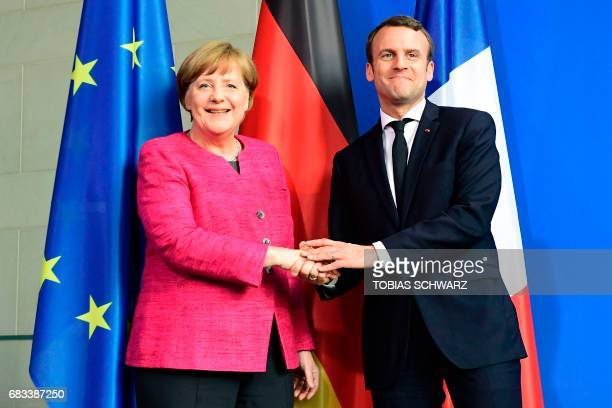 German Chancellor Angela Merkel and French President Emmanuel Macron shake hands after addressing a press conference after talks at the chancellery...