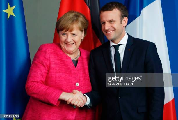 German Chancellor Angela Merkel and French President Emmanuel Macron shake hands after addressing a press conference at the chancellery in Berlin on...