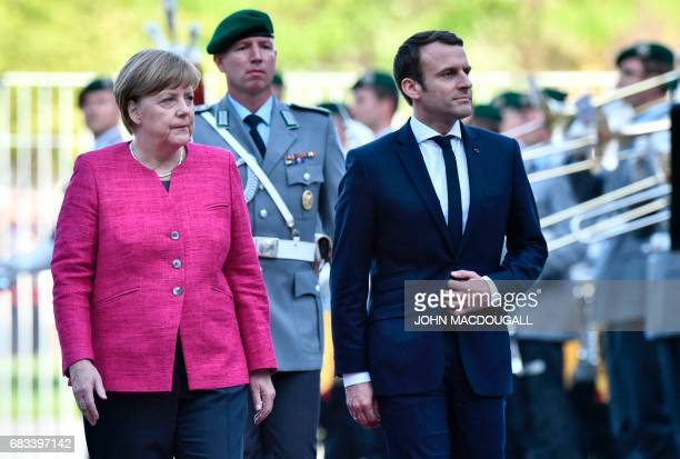 German Chancellor Angela Merkel and French President Emmanuel Macron inspect a guard of honour prior to a meeting on May 15 2017 at the chancellery...