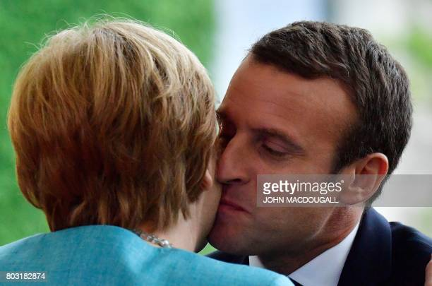 German Chancellor Angela Merkel and French President Emmanuel Macron kiss on June 29 2017 at the Chancellery in Berlin ahead of a meeting with...