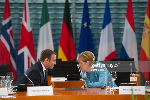 German Chancellor Angela Merkel and French President Emmanuel Macron talk in the conference room during a meeting of EU Leaders before G20 Summit on...