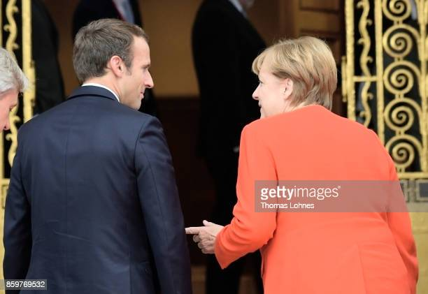 German Chancellor Angela Merkel and French President Emmanuel Macron stand together before bilateral talks while attending the opening of the...