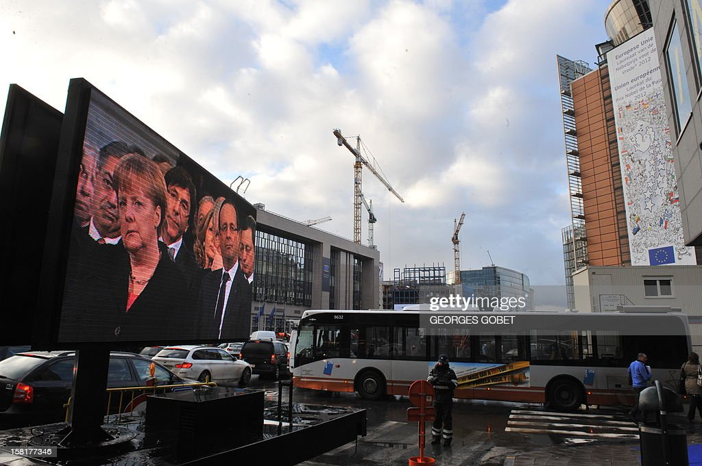 German Chancellor Angela Merkel and French President Francois Hollande appear on a giant screen in front of the European Council during the broadcast of a ceremony for the Nobel peace Prize to European union on December 10, 2012 at the EU Headquarters in Brussels. AFP PHOTO GEORGES GOBET