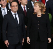 German Chancellor Angela Merkel and French President Francois Hollande arrive for a group photo of the French and German government members at the...