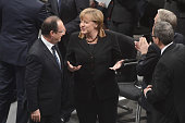 German Chancellor Angela Merkel and French President Francois Hollande chat as they leave after the joint session of the French National Assembly and...