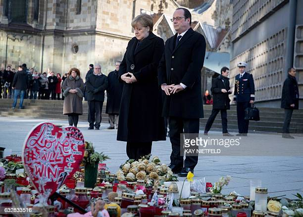TOPSHOT German Chancellor Angela Merkel and French President Francois Hollande lay down flowers at a memorial of flowers and candles for the victims...