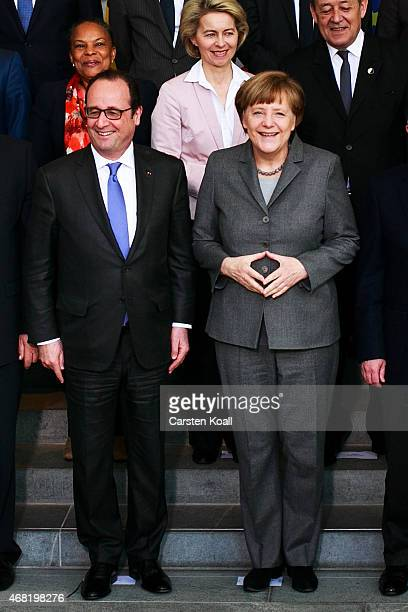 German Chancellor Angela Merkel and French President Francois Hollande pose for a family picture with members of the French and the German cabinet in...