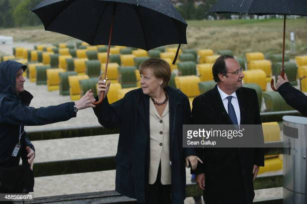 German Chancellor Angela Merkel and French President Francois Hollande walk under umbrellas and rain on a pier on Ruegen Island on May 9 2014 in Binz...