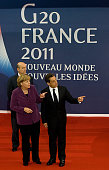 German Chancellor Angela Merkel and French President Nicolas Sarkozy gesture as they arrive for a meeting with the EU and International Monetary Fund...