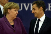 German Chancellor Angela Merkel and French President Nicolas Sarkozy speak to each other as they arrive for a meeting with the EU and International...