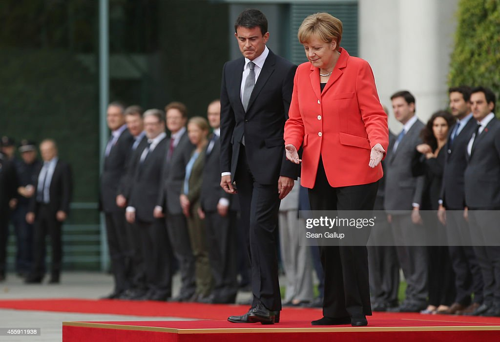 German Chancellor Angela Merkel and French Prime Minister Manuel Valls prepare to review a guard of honour upon Valls's arrival at the Chancellery on September 22, 2014 in Berlin, Germany. Valls is on a two-day visit to Germany at a time when Merkel has been critical of the slow pace of French economic reforms.