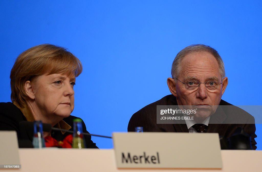 German Chancellor Angela Merkel and German Finance Minister Wolfgang Schaeuble attend a congress of Germany's ruling conservative Christian Democratic Union (CDU) party on December 4, 2012 in Hanover, central Germany. German Chancellor Angela Merkel was re-elected head of her conservative Christian Democrats (CDU) by more than 97 percent of delegates' votes at a two-day party congress. It was Merkel's best result since she took over as chairman of the CDU in 2000 and comes as she gears up for fighting for a third term at the helm of Europe's top economy in elections expected in September 2013. AFP PHOTO / JOHANNES EISELE